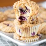 The BEST Blueberry Banana Yogurt Muffins! Topped with a crunchy cinnamon sugar topping and filled with blueberries and chocolate chips!