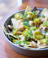 Cilantro Lime Chicken Nachos: lime and blue tortilla chips are topped with cilantro lime grilled chicken, homemade cheese sauce, jalapeños and green onions. Simple but crazy good.