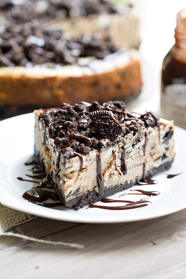 The BEST Peanut Butter Oreo Cheesecake. This creamy peanut butter cheesecake is filled and topped with Oreo cookies and drizzled with hot fudge! | This Gal Cooks
