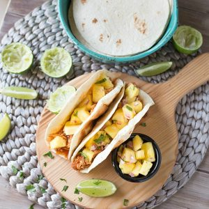 Shredded Chicken Tacos are a simple and delicious dinner recipe that's made in your slow cooker. The tacos are topped with an out of this world fresh homemade pineapple salsa!
