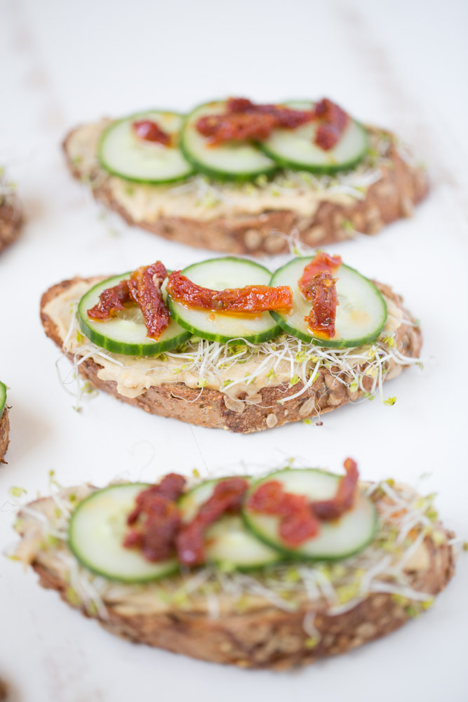 Roasted Garlic Hummus Toast with broccoli sprouts, cucumber and sundried tomatoes | This Gal Cooks