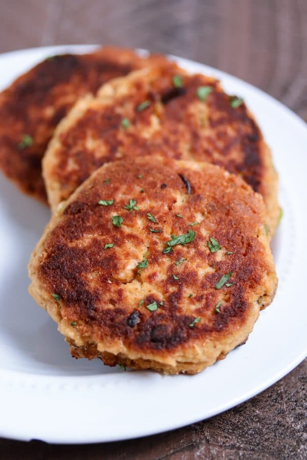 The easiest salmon cakes you'll ever make! These paleo salmon cakes are made with canned salmon, paleo mayo, spices, and almond flour! Serve them as an appetizer or with your favorite veggie for a complete healthy meal. #paleo #salmon #savory #dinner #appetizer
